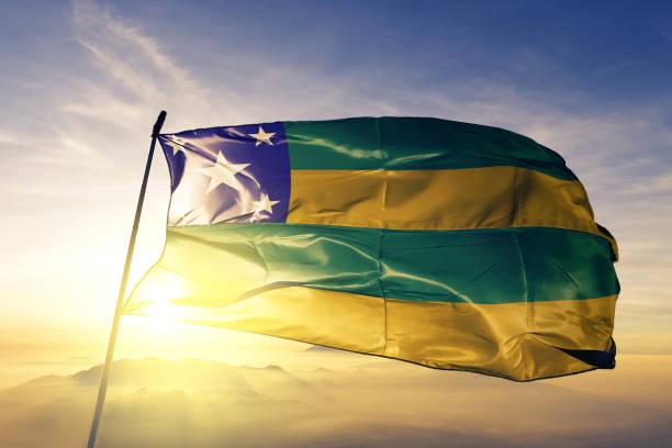 Sergipe state of Brazil flag textile cloth fabric waving on the top sunrise mist fog stock photo