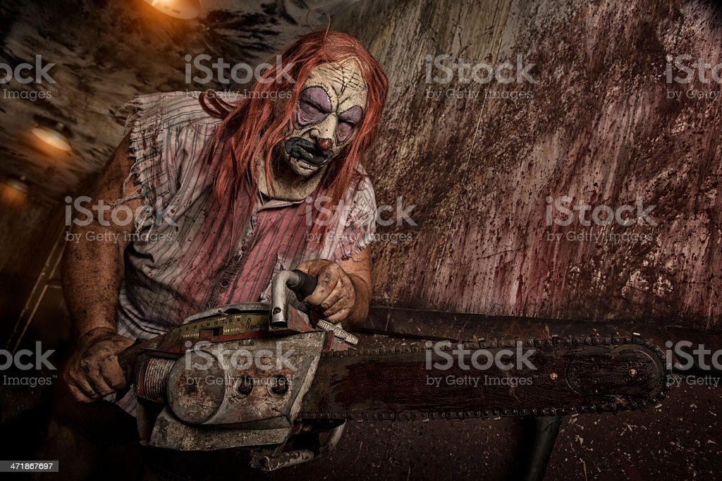 Serial Killer Clown holding chain saw royalty-free stock photo