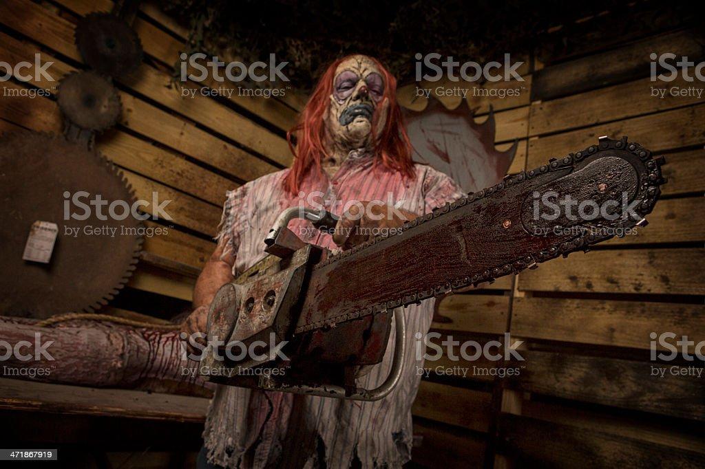 Serial Killer Clown holding chain saw stock photo