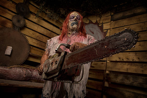 serial killer clown holding chain saw - chainsaw stock photos and pictures