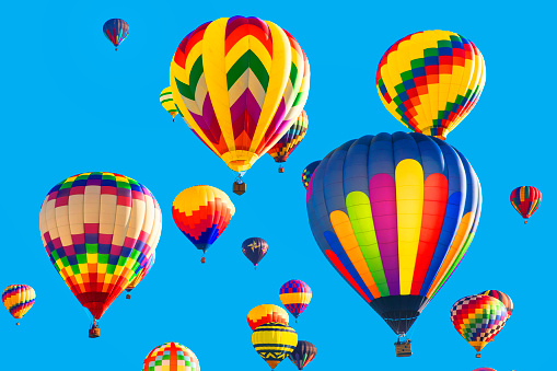 Series: Colorful hot air balloons flying in bright blue sky