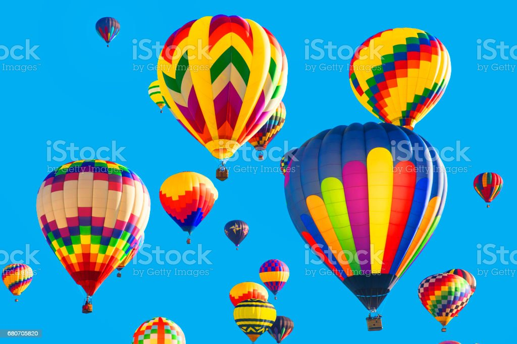 Series: Colorful hot air balloons flying in bright blue sky stock photo