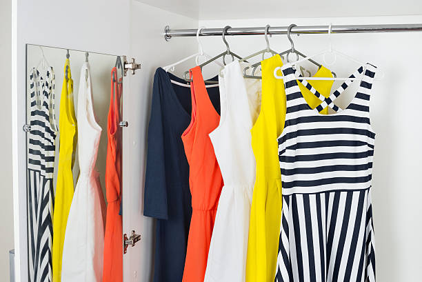 series of bright modern fashion women dresses on hangers stock photo