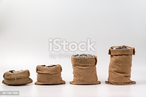 482747823istockphoto Series of coins bags made from hemp sack full with coins 947367990