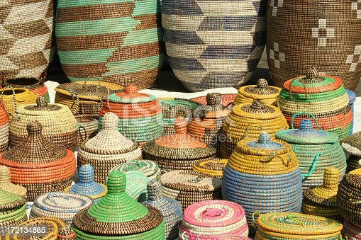 These colorful woven African seagrass storage baskets are handmade by women in Senegal, Congo, and Angola. The baskets are made from natural dried sea grass and are colored using natural dyes. The designs are ethnic in origin. The baskets seen here are on display in a street market.