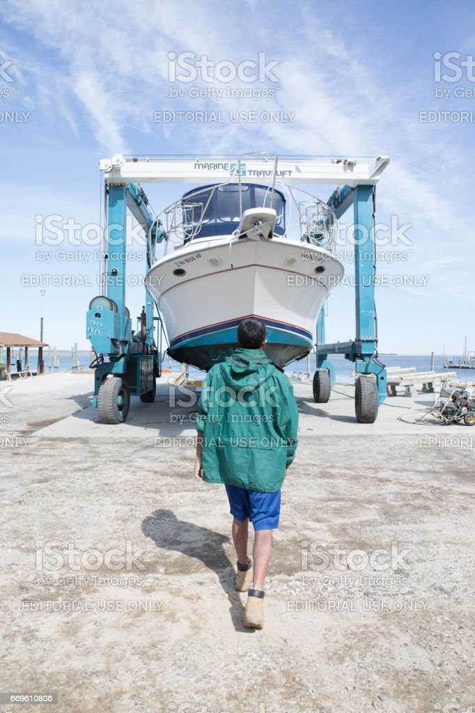 Series: Yacht being taken out of the water with a marine travel lift. stock photo