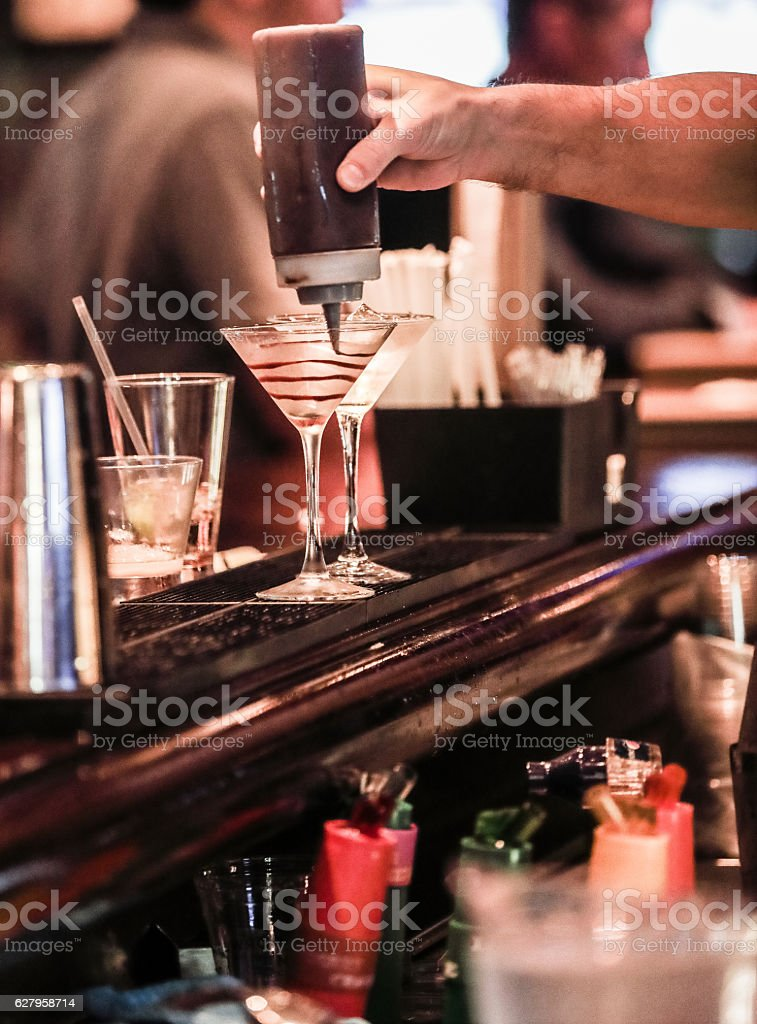 Series:Bartender preparing a chocolate martini in classic martini glass stock photo