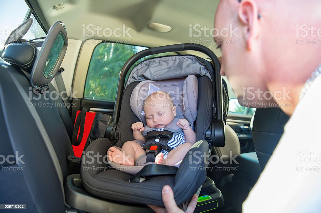 Series:Father puts sleeping baby in car seat into car stock photo