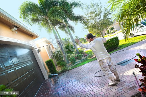 Hispanic male power washing an upscale home beore painting in a 55+ senior gated community. Taken with a Canon 5D mark IV