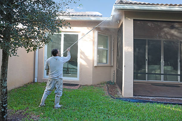 series:hispanic worker power washing back of one story home - high pressure cleaning stock photos and pictures
