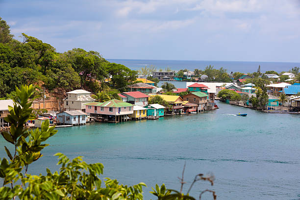 Series:Honduran island of Roatain in the Caribbean *3 logo rule. Scenic view of a seaside village on  Roatain, which is part of the Bay Islands of Hondouras. It is the largest of the Bay Islands and an eco-tourism destination. Colorful wooden stilt homes dot the landscape. Taken with Canon 5D Mark lV. roatan stock pictures, royalty-free photos & images