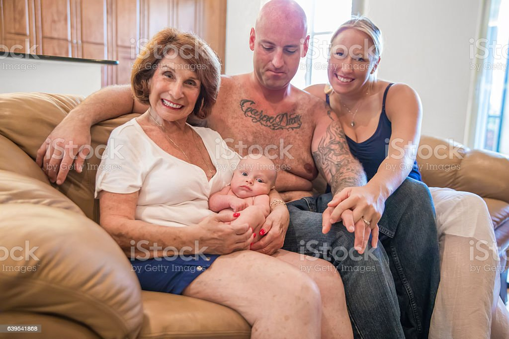 Series:Proud grandmother holds six week old grandson with his parents стоковое фото