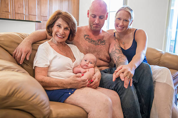 series:proud grandmother holds six week old grandson with his parents - alte tattoos stock-fotos und bilder