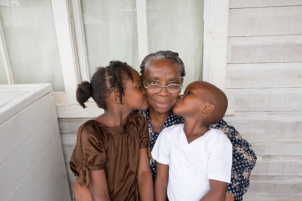 Series:Proud Honduran grandmother getting kiss from grandchildren Portrait of senior Honduran woman in her sixties with her young granddaughter and grandson. They live on the island of Roatan in a shanty town. She is sitting with her arms around them and they are giving her a kiss on the cheek. They are outside their house. There is a washing machine on the front porch. Taken with Canon 5D Mark lll. poverty stock pictures, royalty-free photos & images