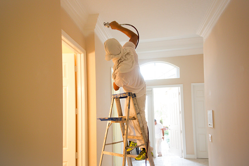 Real house painter using spray paint gun to paint the crown molding on the ceiling in home. He's standing on a ladder.  His face and head are covered for his protection.  He is in the hallway. Another painter is at the front door. Taken with a Canon 5D Mark 3.