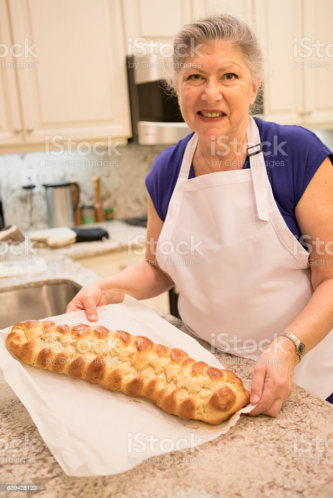 Series:Senior woman showing off her baked breaded challah stock photo
