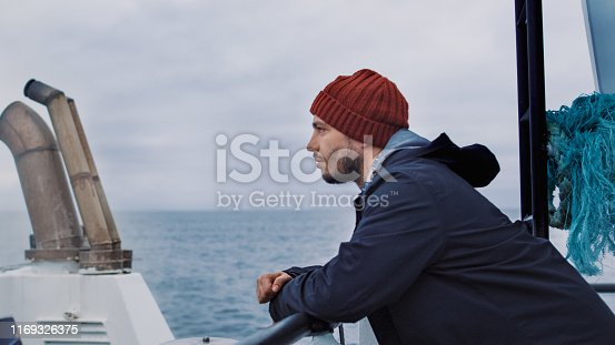 Serios Man Stands on the Ship and Looks At the Sea.