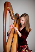 Serious 12-year old girl playing a harp on grey background.