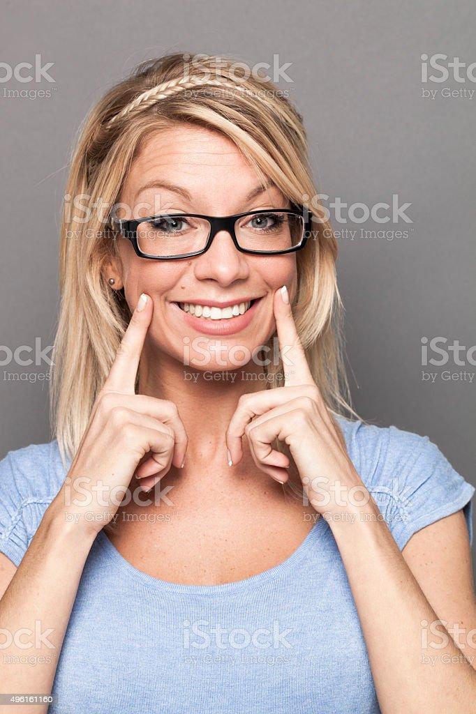 serious 20s blonde girl expressing joy with fake smile stock photo