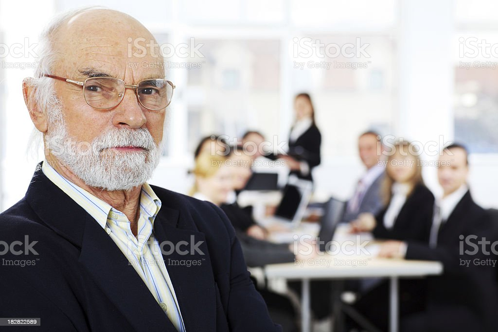 Serious academic with graduates behind his. royalty-free stock photo