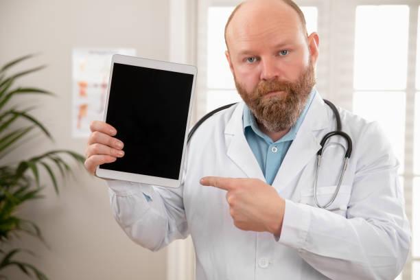 Seriöser erwachsener männlicher Arzt, der ein digitales Bild oder einen Bericht auf einem Tablet zeigt – Foto