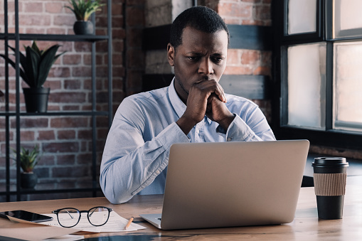 530281733 istock photo Serious african american business man working on project at modern loft office, thinking about financial troubles 1156514370