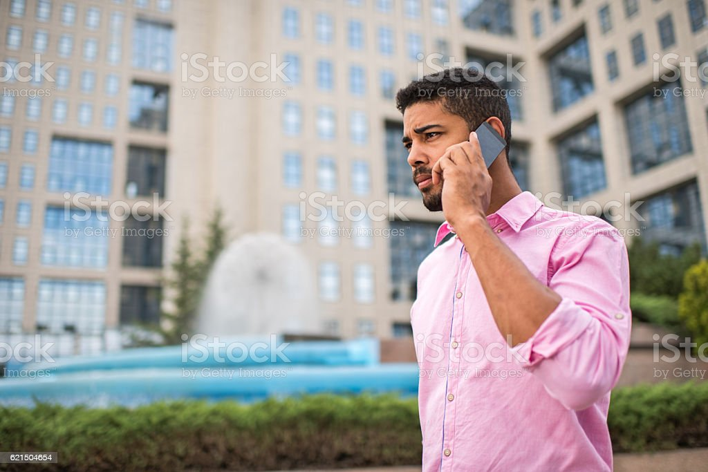 Serious African American businessman communicating over smart phone outdoors. photo libre de droits