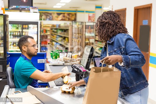 istock Serious African American cashier scanning goods at checkout 1194837504