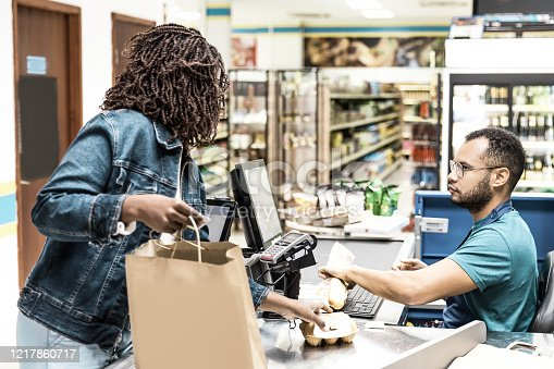 istock Serious African American cashier scanning goods at checkout 1217860717