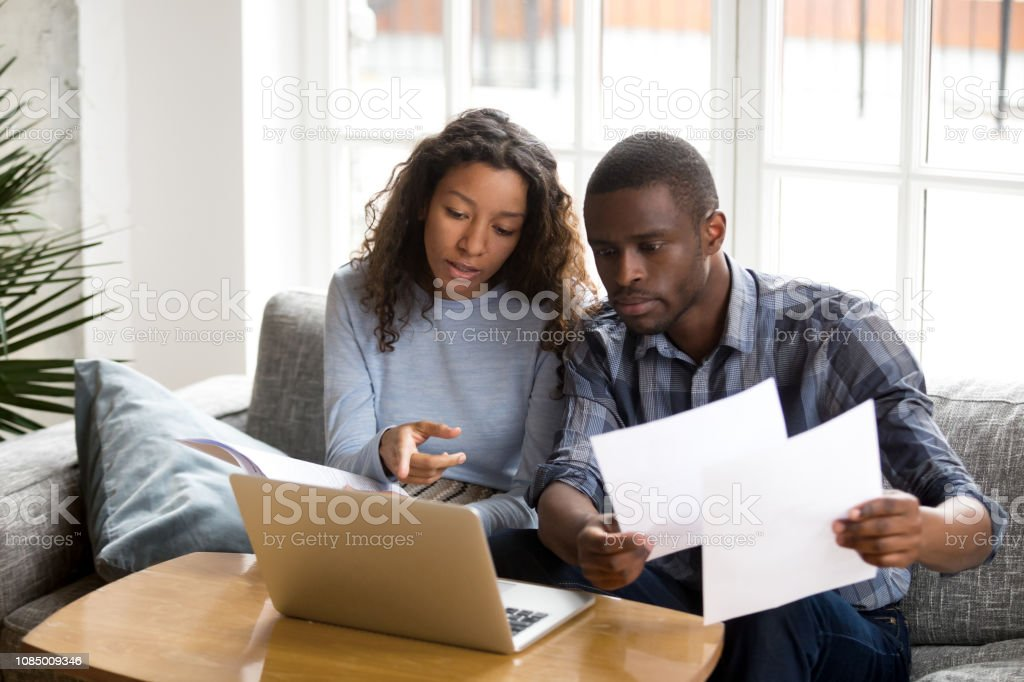 Serious African American couple discussing paper documents Serious African American couple discussing paper documents, sitting together on couch at home, man and woman checking bills, bank account balance, terms of contract, mortgage, loan agreement Adult Stock Photo