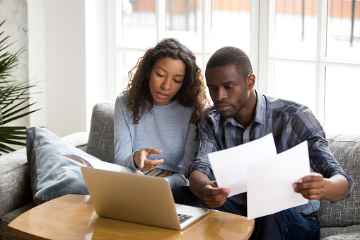 Serious African American Couple Discussing Paper Documents Stock Photo - Download Image Now