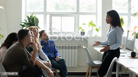 1085713886 istock photo Serious african american female leader, mentor holding briefing for team. 1257948576