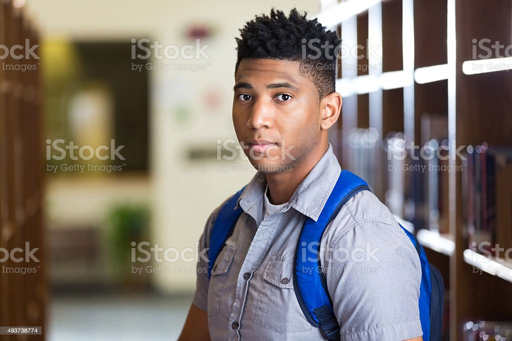 Serious African American high school boy in library stock photo