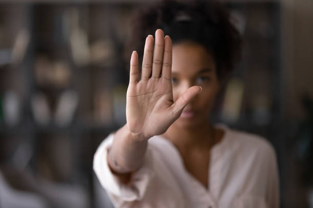 Serious african american woman protesting against bullying. stock photo