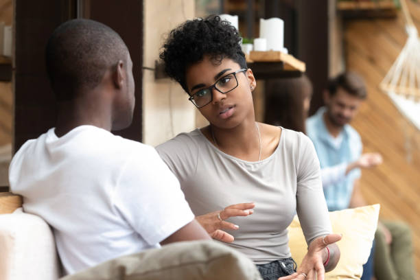 Serious African American woman talking with man in cafe stock photo