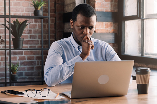 530281733 istock photo Serious african business man working on project at modern loft office, thinking about financial troubles 1151641779