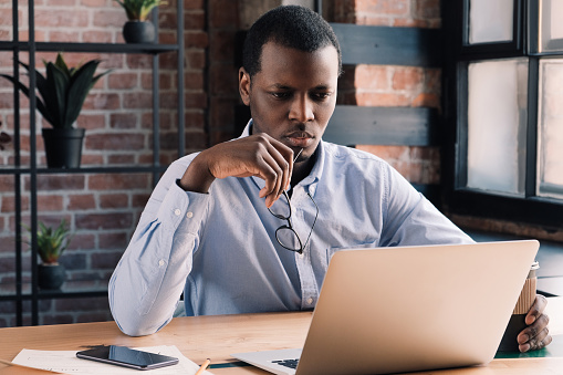 530281733 istock photo Serious african business man working on project at modern loft office, thinking about financial problems 1163183092
