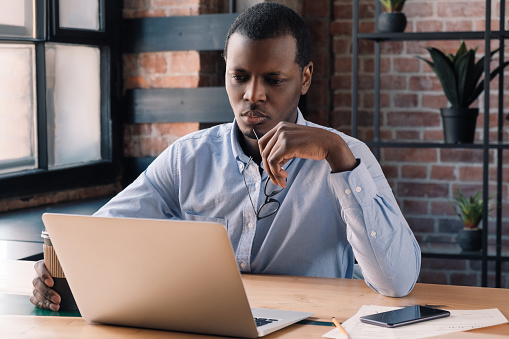 530281733 istock photo Serious african businessman working on project at modern loft office, thinking about financial troubles 1161788048
