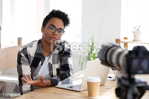 Serious african girl youtuber blogger vlogger talking to camera shooting educational video filming webinar blog, black female business coach teacher speaking recording vlog training or job interview