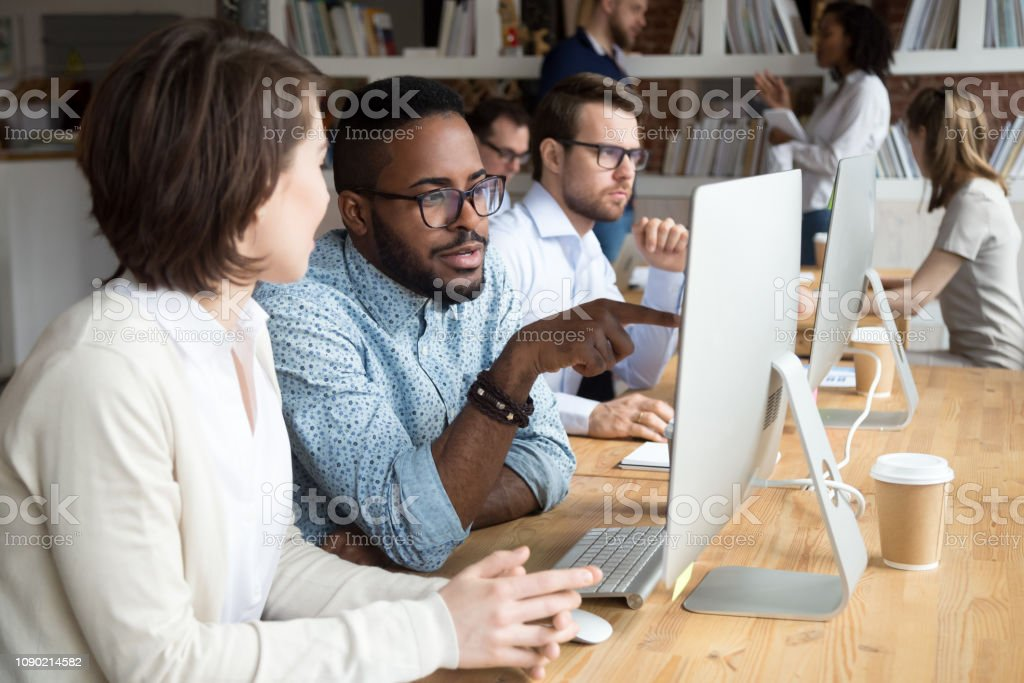 Serious african office worker explaining coworker new online project Serious african office worker explaining coworker new online project, diverse colleagues discuss idea working together on computer in office, black mentor helping colleague with pc in coworking space A Helping Hand Stock Photo