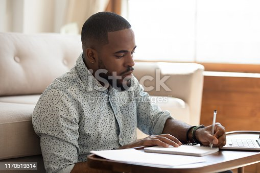 1083827722 istock photo Serious african student writing notes studying at home with laptop 1170519314