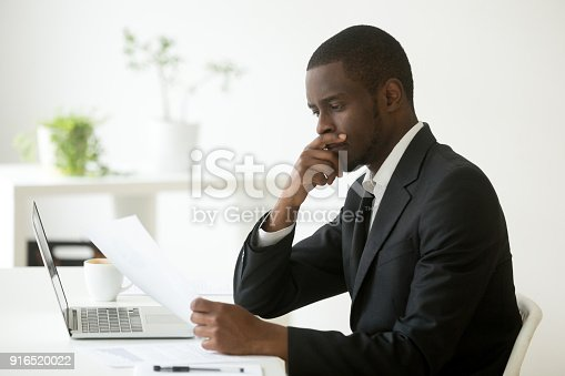 istock Serious african-american businessman thinking of notice reading letter at workplace 916520022