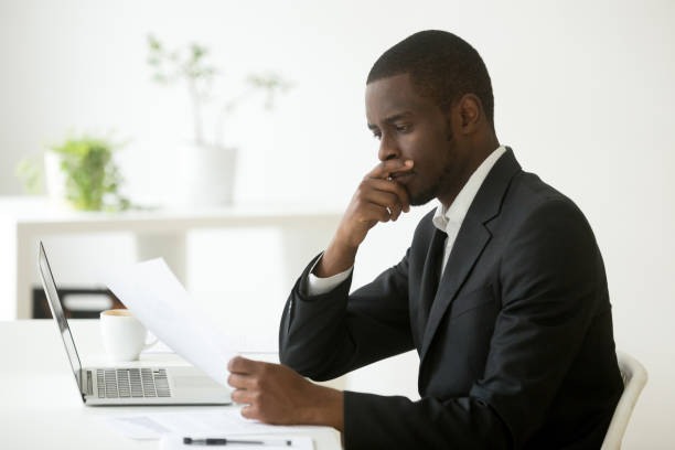 Serious african-american businessman thinking of notice reading letter at workplace stock photo
