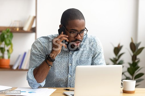 istock Serious african-american employee making business call focused on laptop screen 1156269809