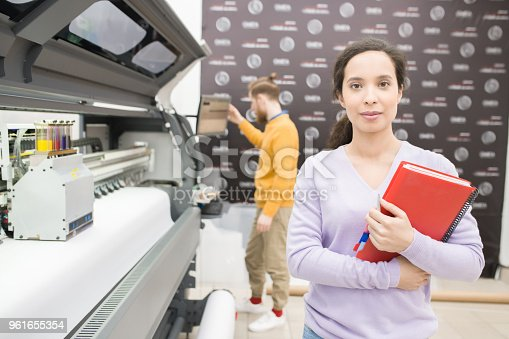 istock Serious African-American female print production manager with spiral diary standing at large plotter machine and looking at camera in printing shop 961655354