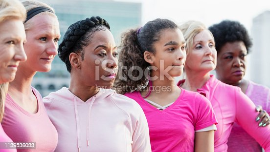 istock Serious African-American woman with group wearing pink 1139536033
