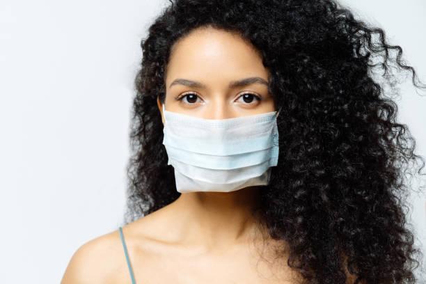 une femme afro-américaine grave tente d'arrêter le virus et la maladie épidémique, reste à la maison pendant l'épidémie infectieuse, porte un masque médical, isolé sur le fond blanc, hospitalisé, diagnostiqué - fond blanc photos et images de collection