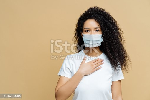 Serious Afro American woman wears medical face mask, has problems with breathing, presses hand to chest, got infected with coronavirus, isolated on beige ackground. Covid 19, health care concept