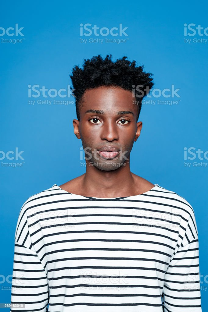 Serious afro american young man Portrait of serious afro american guy wearing striped long sleeved t-shirt, looking at camera. Studio shot, blue background.  Adult Stock Photo