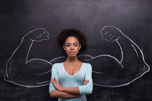 istock Serious afro-american woman with painted muscular arms on chalkboard 465667602